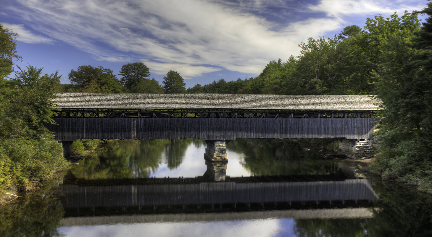 Covered bridge over water on a sunny day
