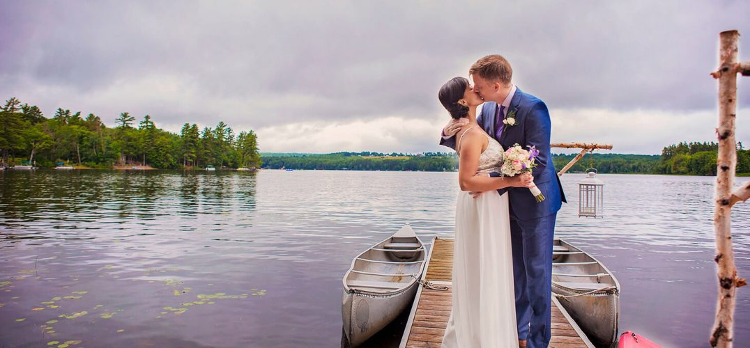 Newlywed couple kissing on a small dock