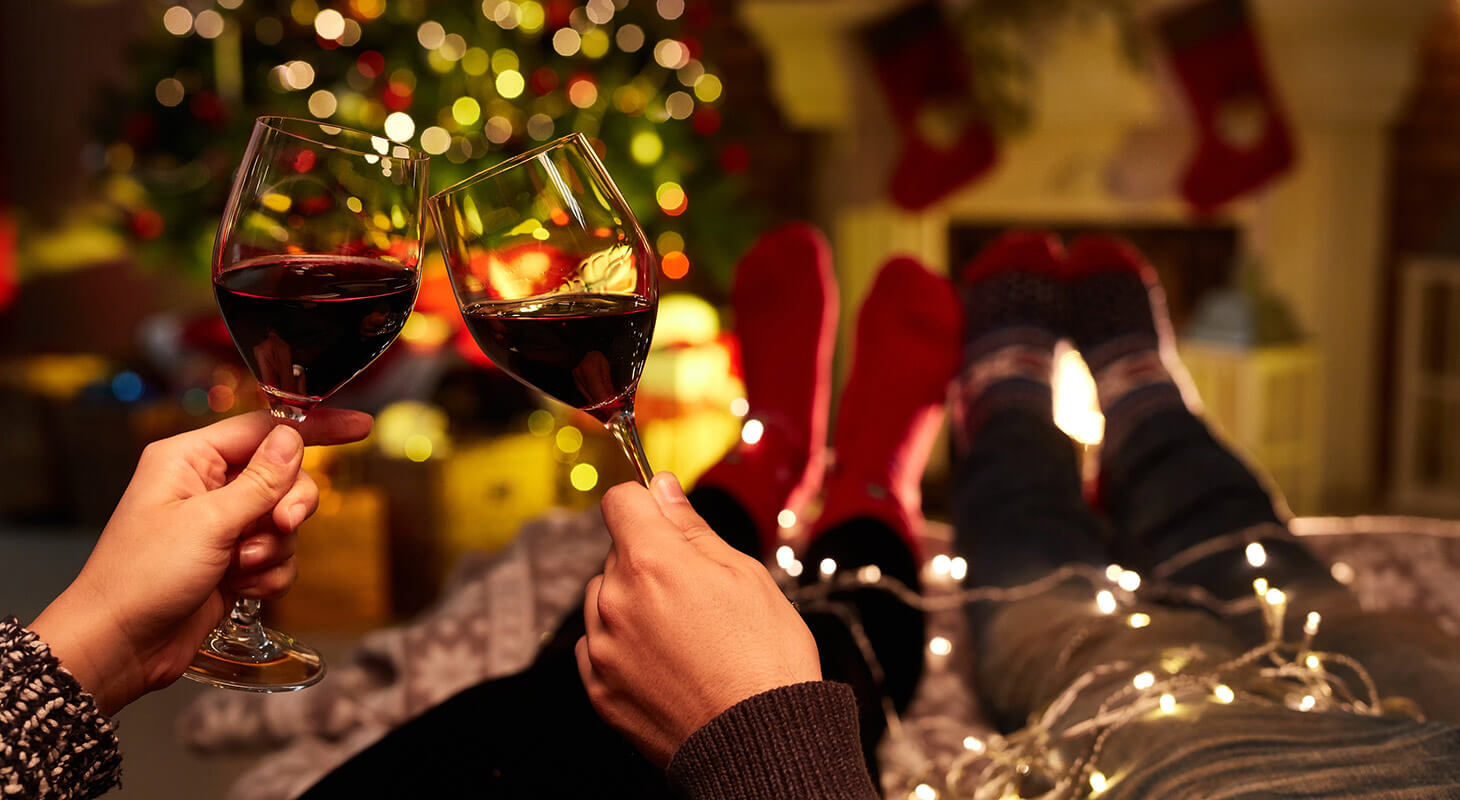 Couple toasting wine glasses with holiday decorations all around