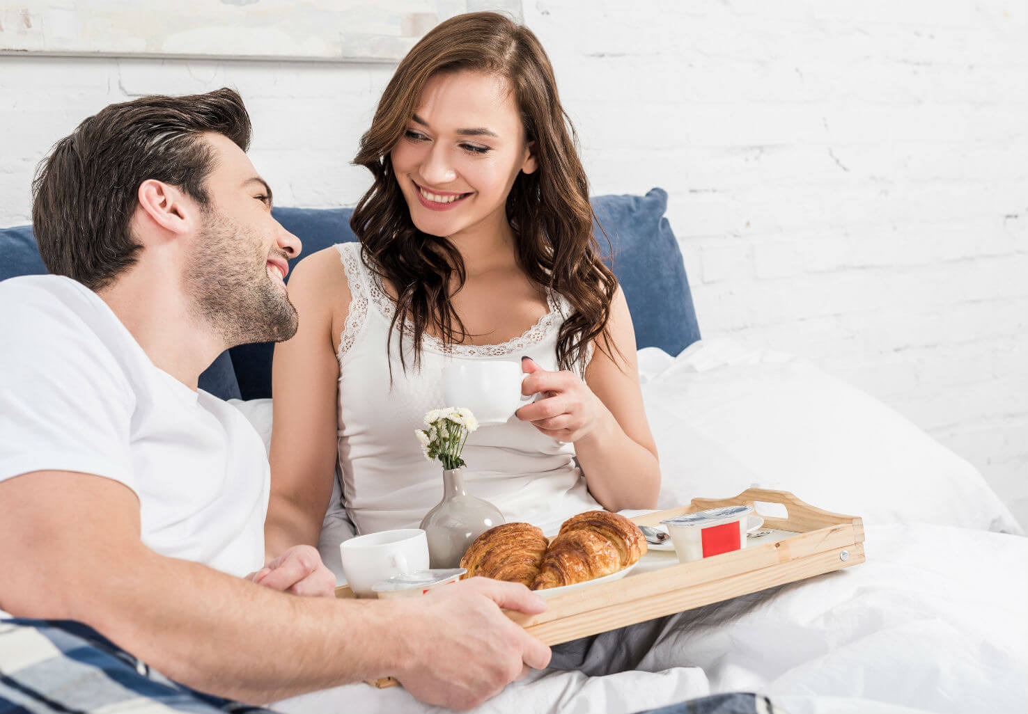 Couple relaxes happily with breakfast in bed