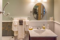 Close-up shot of a full bathroom sink, mirror and towel rack