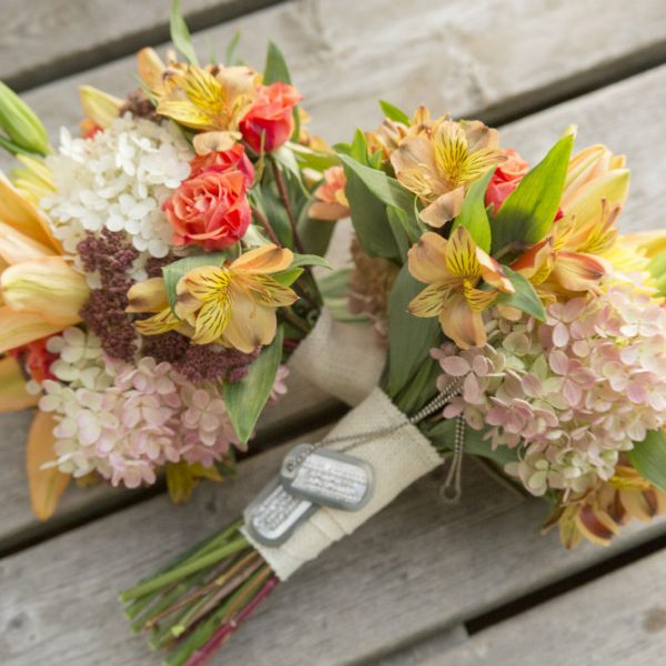 Two elopement bouquets, one with dog tags on it, sitting on a dock
