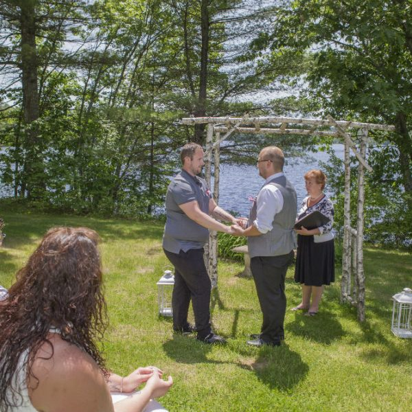 Two gay grooms exchanging vows in the summer overlooking the lake