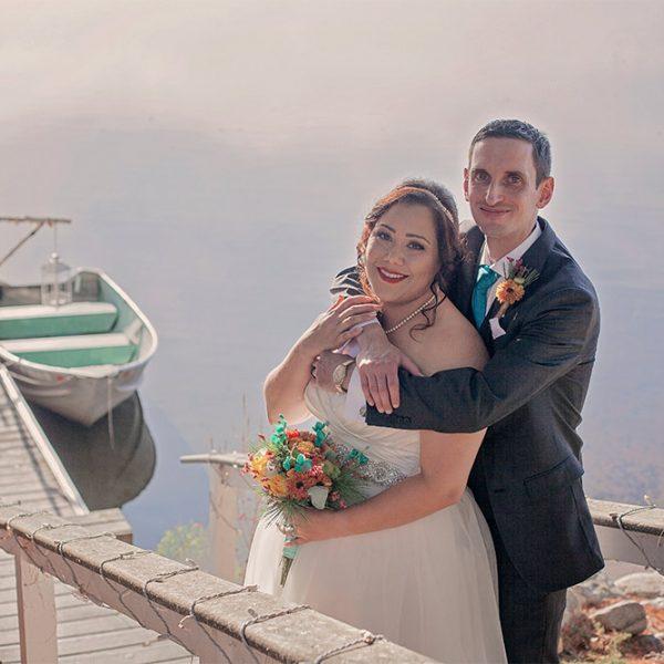 Groom hugs bride on dock on Tripp Lake in the summer