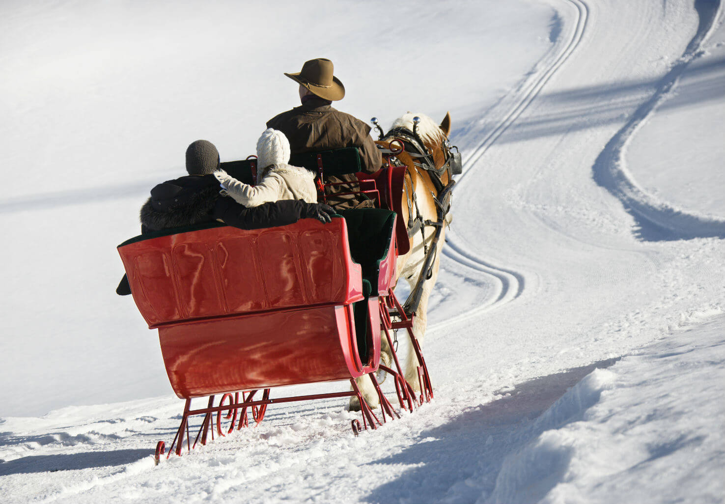 Couple going for a sleigh ride across a snowy trail