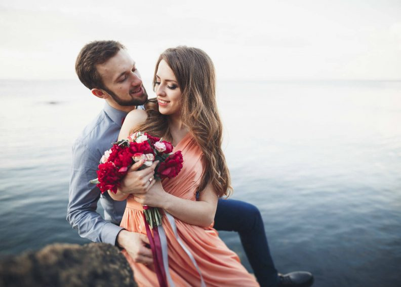 Couple enjoying bouquet by lake