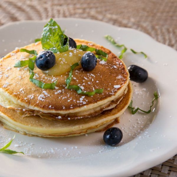 Pancake stack seasoned with powdered sugar and blueberries