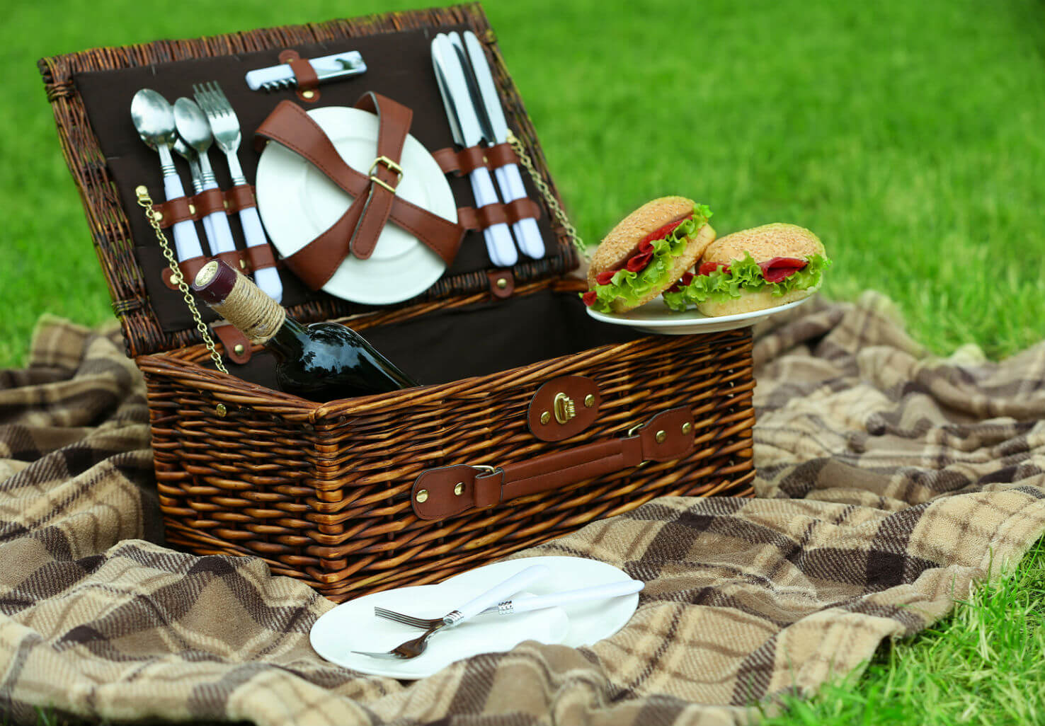 Picnic basket with sandwiches, wine, plates, and silverware