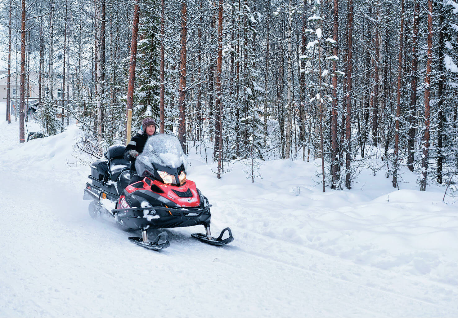 Man riding snowmobile across trail through forest