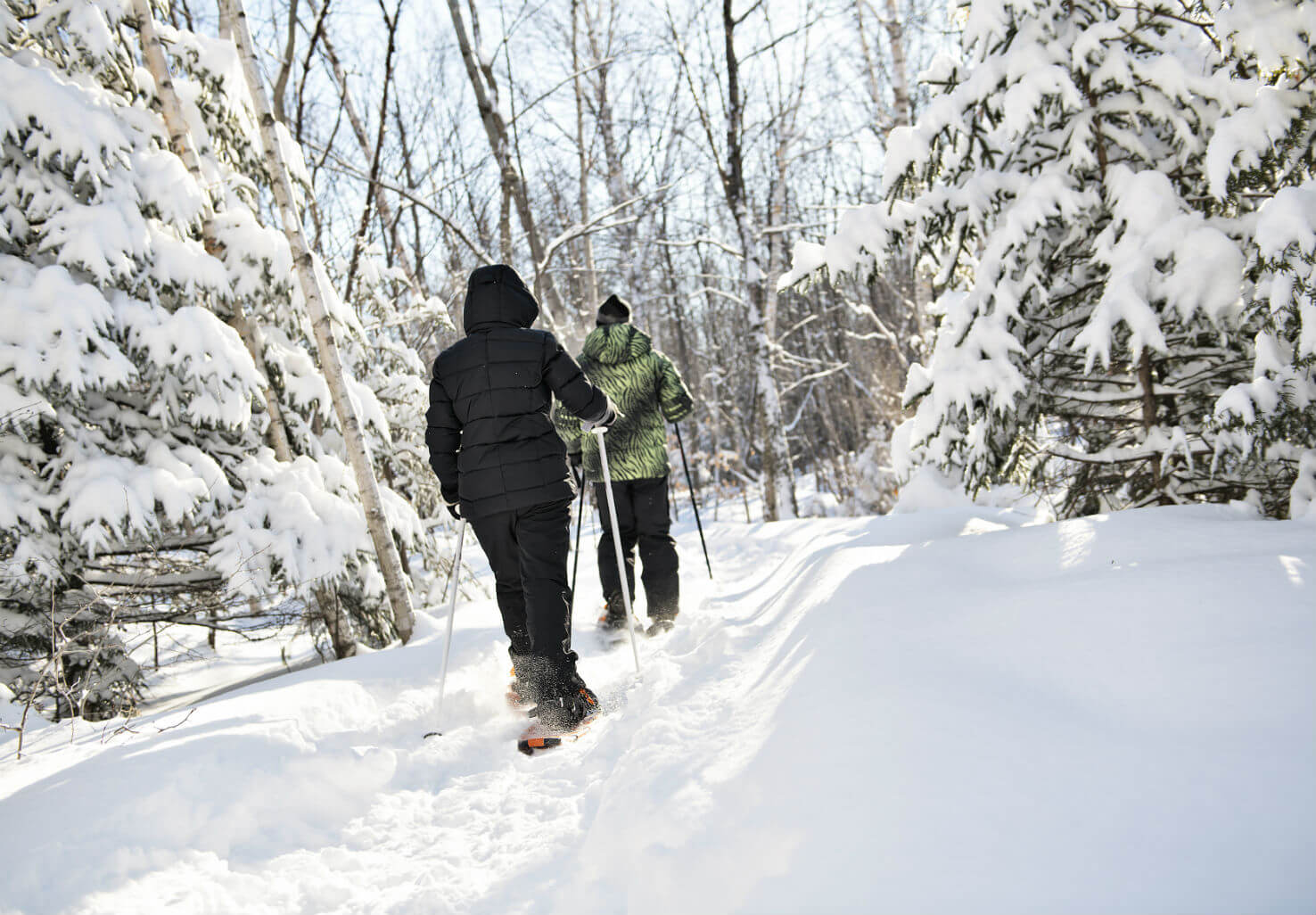 Couple goes snowshoeing through woods