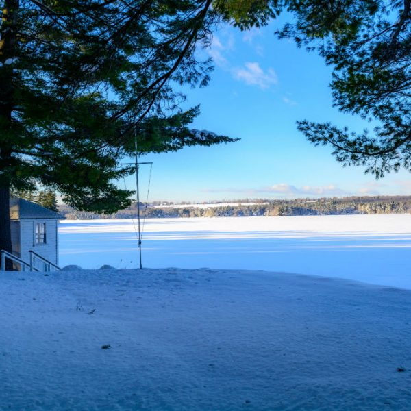Tripp lake and beach covered in snow by the Boat House Bistro