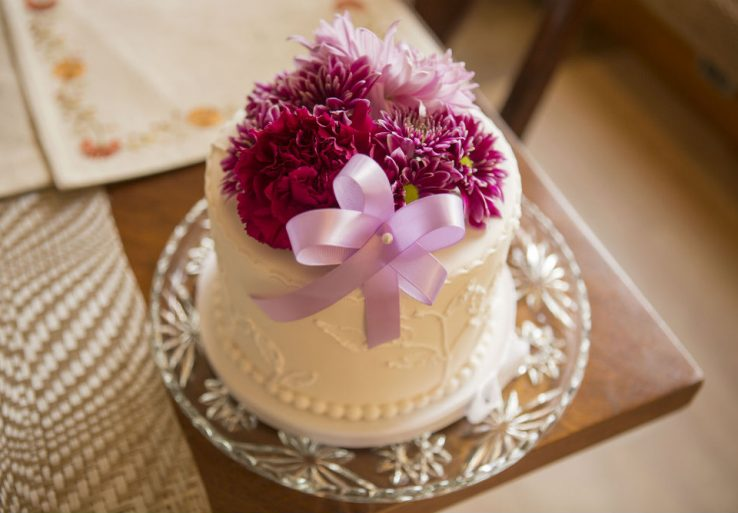 Small wedding cake covered in flowers created by local, Winey Baker