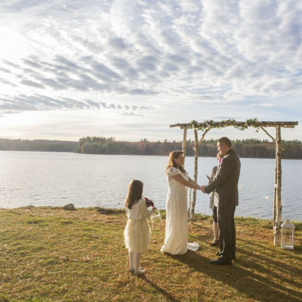 Bride and groom standing together near daughter at intimate lakeside elopement