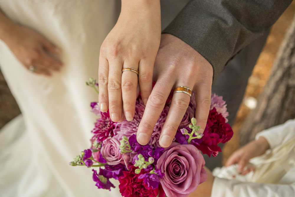 Bride's and groom's hands resting on bouquet
