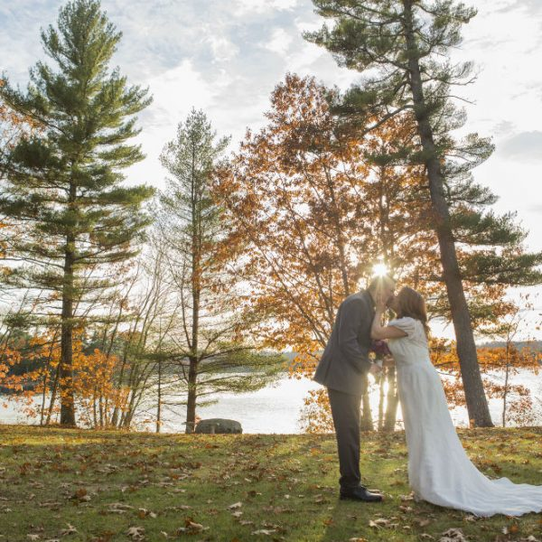 Bride and groom kiss in field among fall foliage