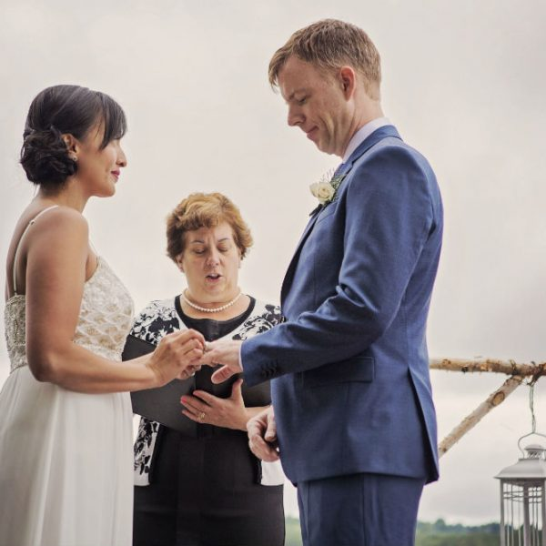 Bride and groom exchange rings on dock at wedding