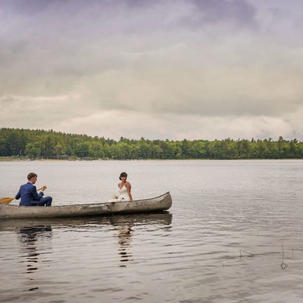 Newlyweds rowing canoe across lake in the summer