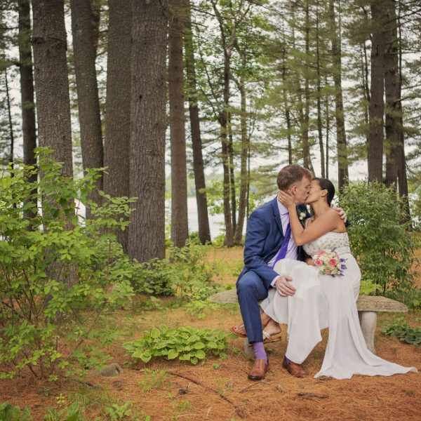 Bride and groom kiss on stone bench in grove