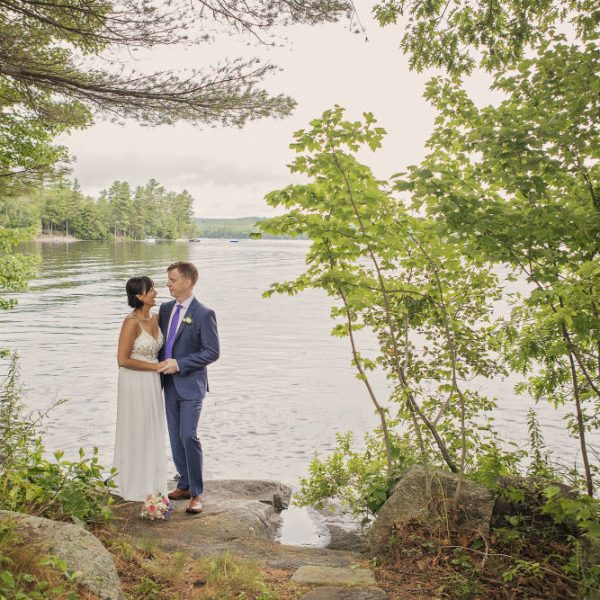 Bride and groom embrace in a grove by the lake