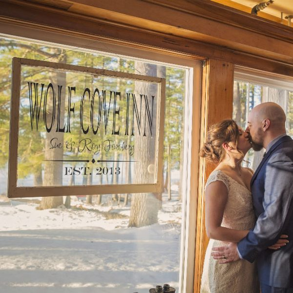 Couple kissing by the Wolf Cove Inn sign at a winter elopement