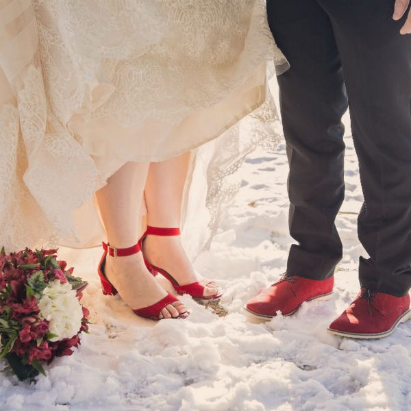 Bride and Groom stand together in bright red shoes in the snow