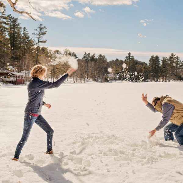 Newlywed couple having a snowball fight on Tripp Lake