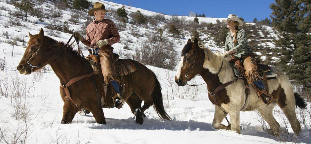 Man and woman riding horses through snow
