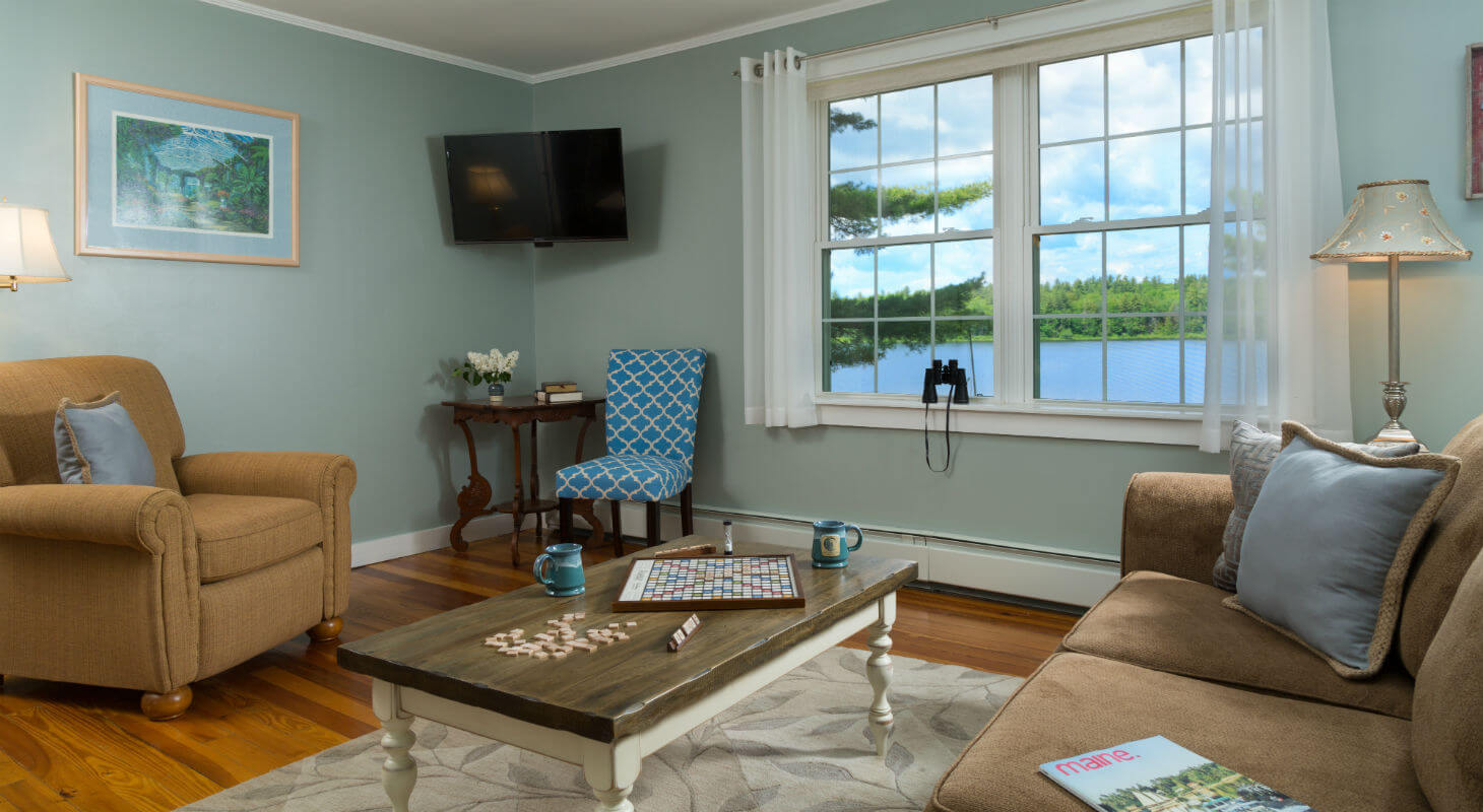 Sitting area with board games and coffee mugs out by television and large window