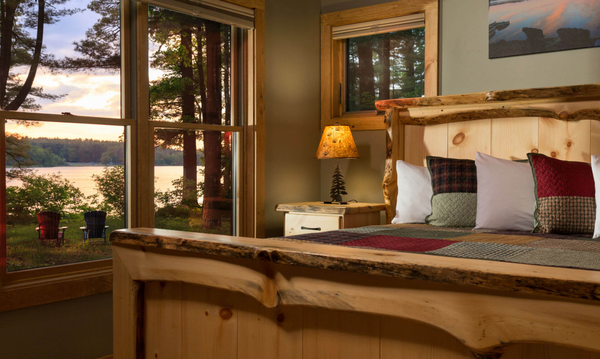 Cozy cabin bed by window with lake view