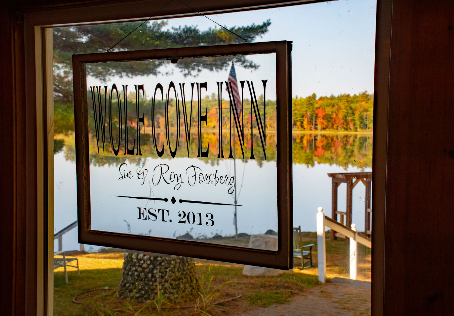 "Sign in a window reading ""Wolf Cove Inn - Sue & Roy Foresburg"" overlooking lake in the fall"