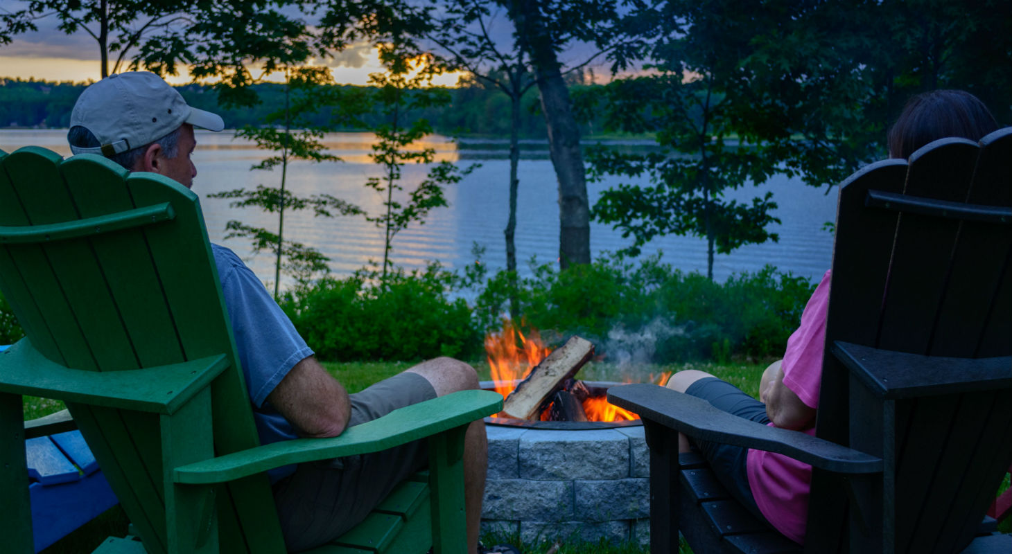 A couple sits next to fire at sunset