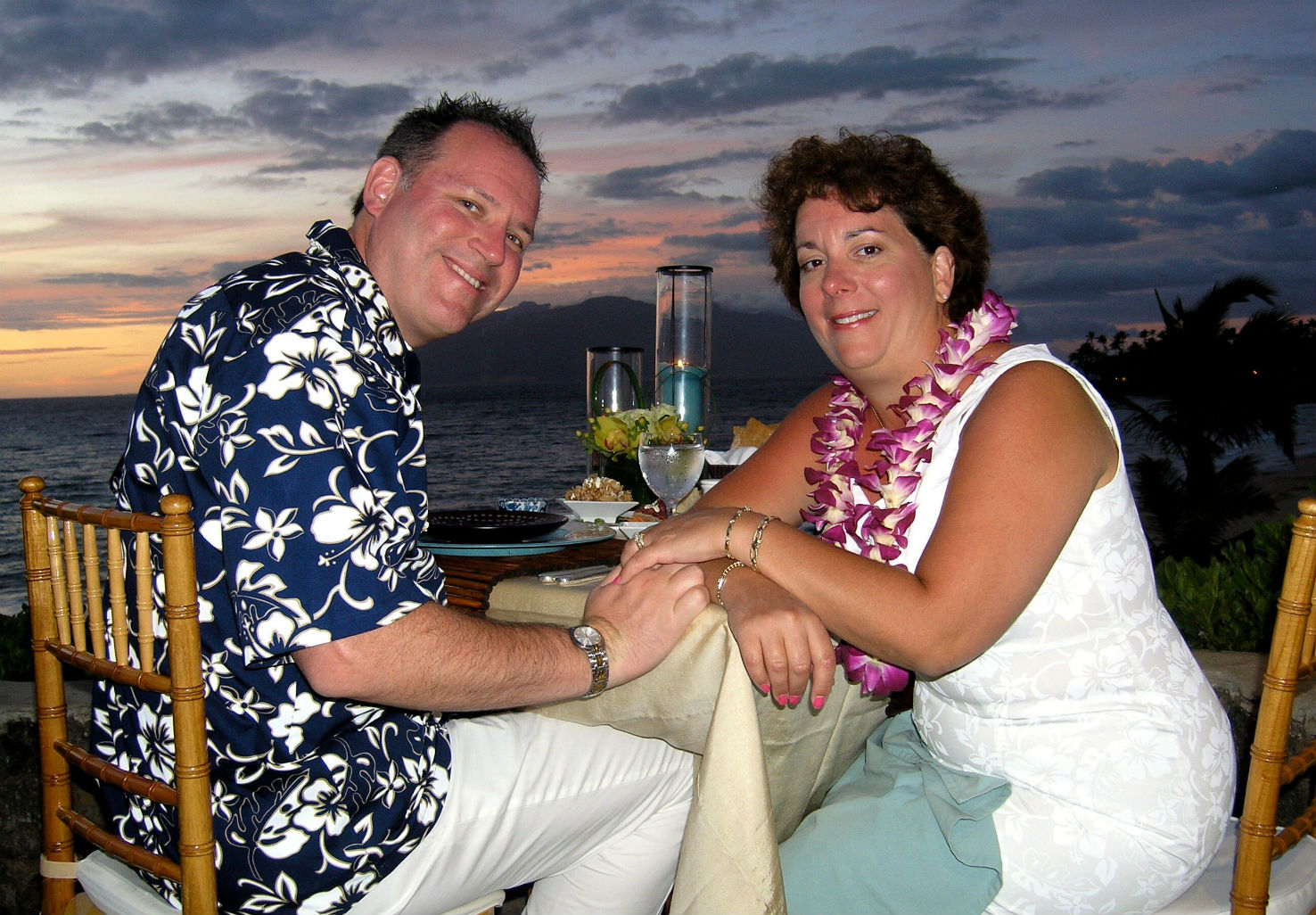 A brunette couple sitting at a table at sunset while holding hands