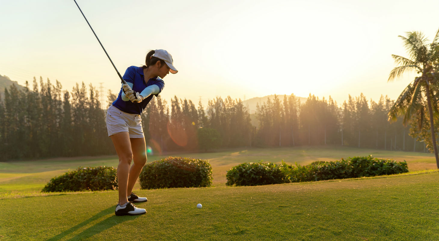 Young golfer winds up to swing her club in the morning