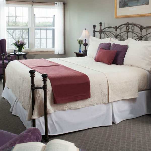 Soft bed with fresh linens by two antique chairs provide the perfect Maine accomodations