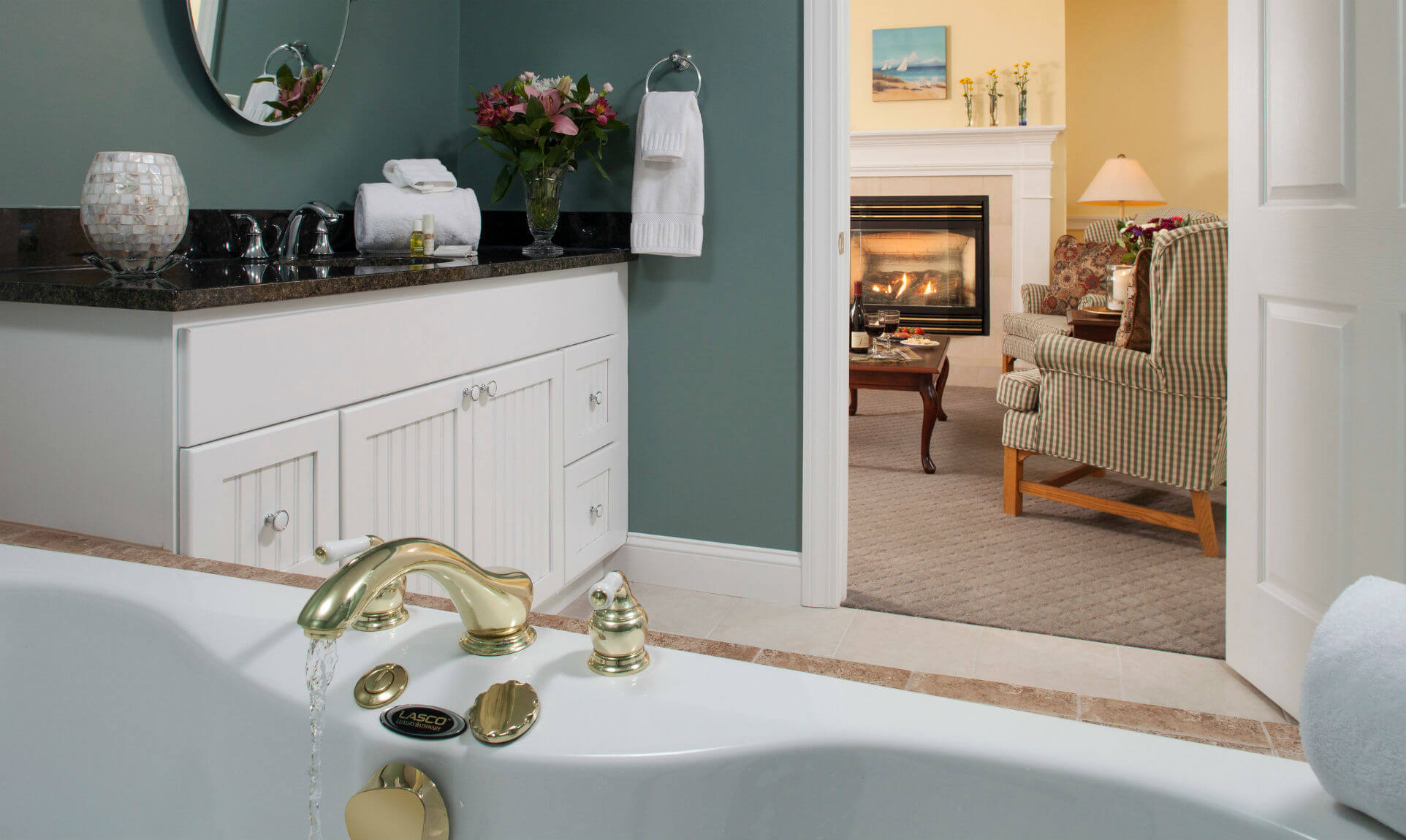 Shot from above bathtub showing showing bathroom counter and sitting area with fireplace through doorway