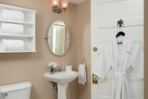 A bathrobe hangs on the bathroom door by the sink and toilet