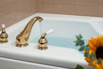 Close-up shot of a full bathtub with a brass faucet near flower vase