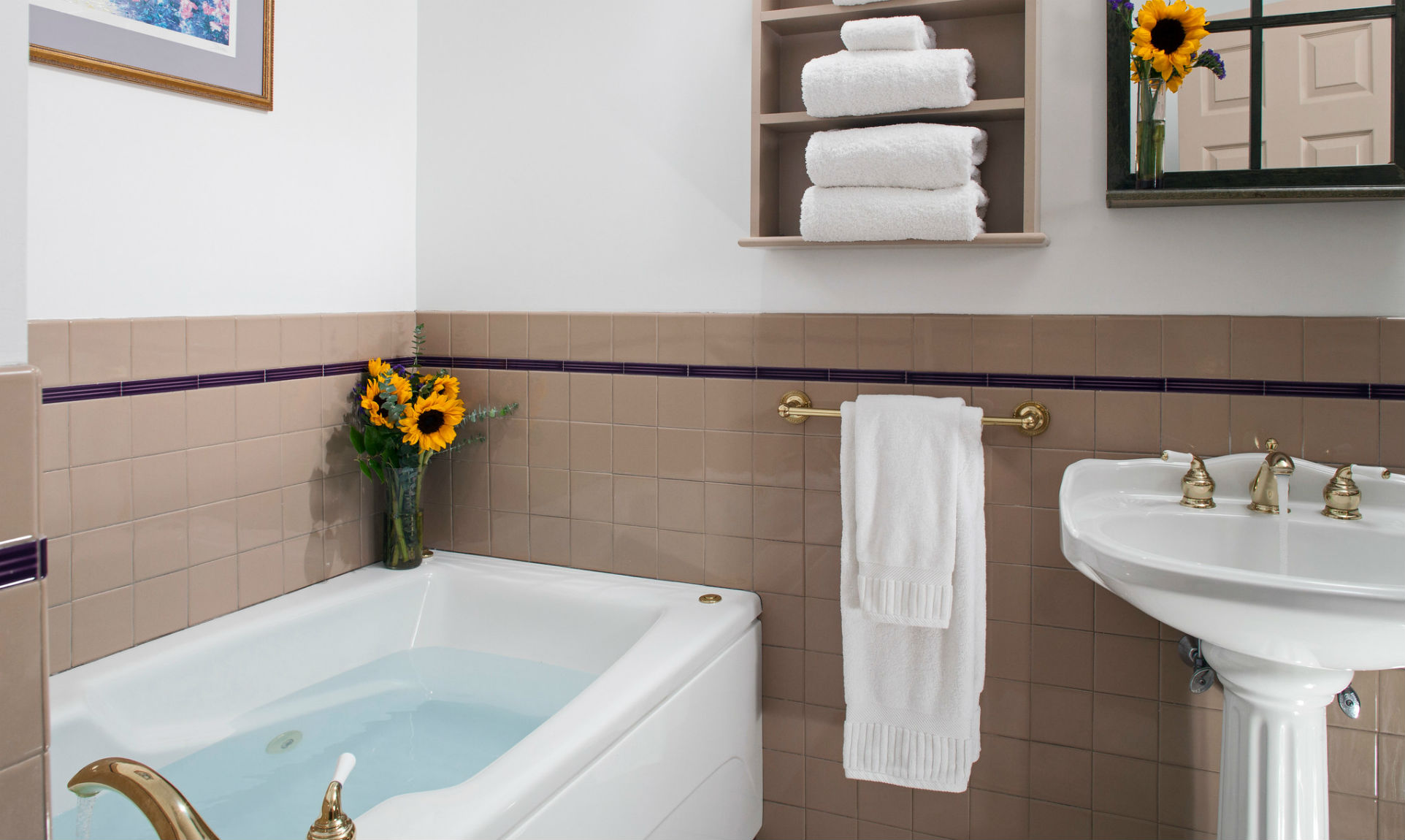 Full, warm bath with flower vase next to towel rack and sink