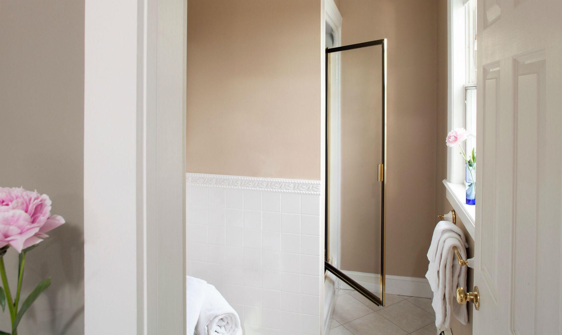 Open shower door at the end of the bathroom