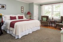 Soft king bed with maroon linens next to sitting area