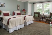 Two soft twin beds with maroon linens next to sitting area