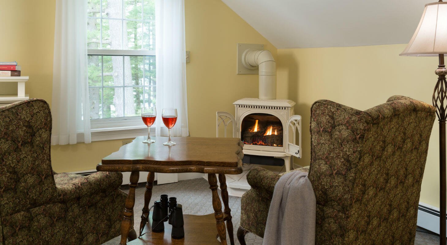 Sitting area with wine on antique table near fireplace