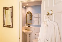 Entrance to bathroom with bathrobe, mirror, sink, and toilet