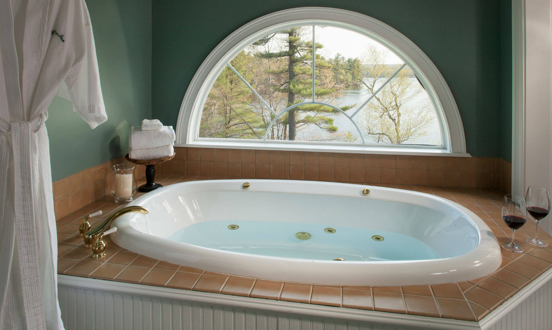 Shot of the filled warm bath tub and bathrobe next to the window overlooking Tripp Lake