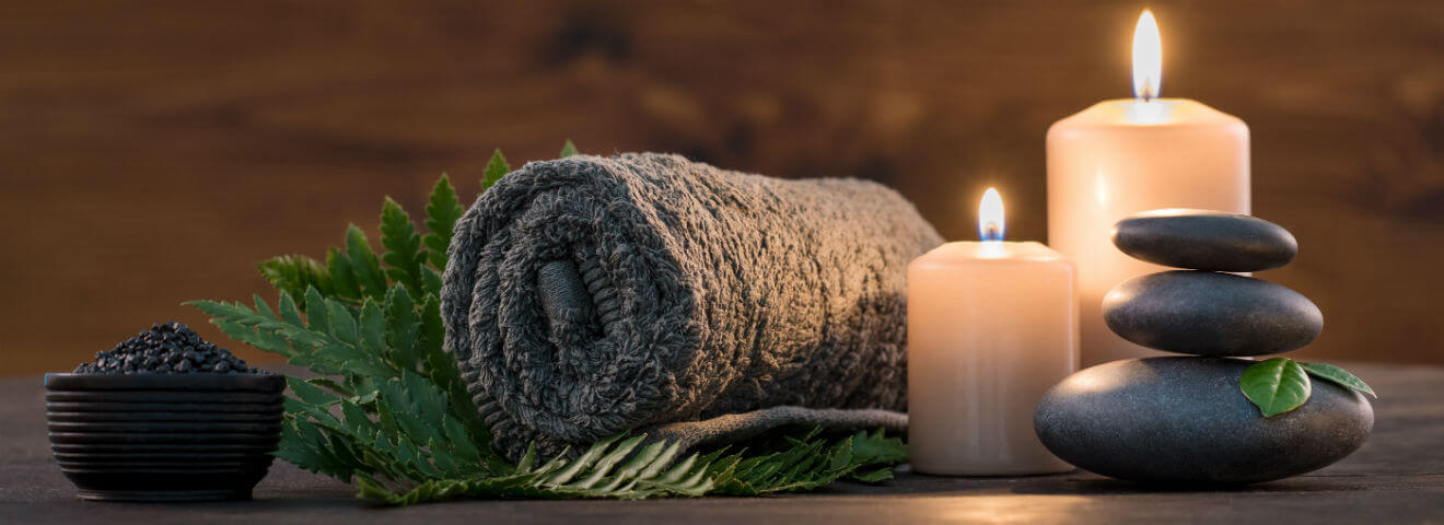 Candles burning next to hot rocks and a warm towel sitting on a fern