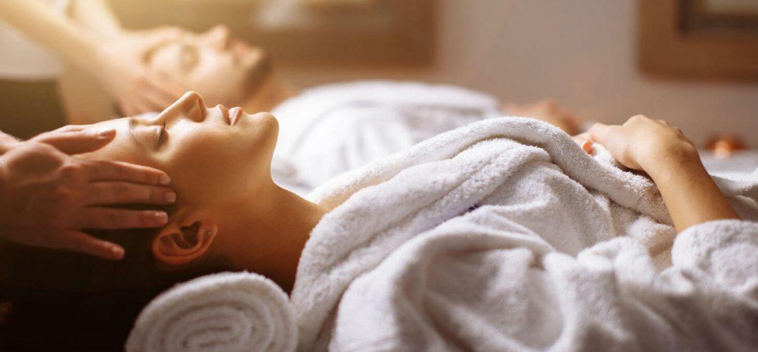 Couple in bathrobes receive head massage