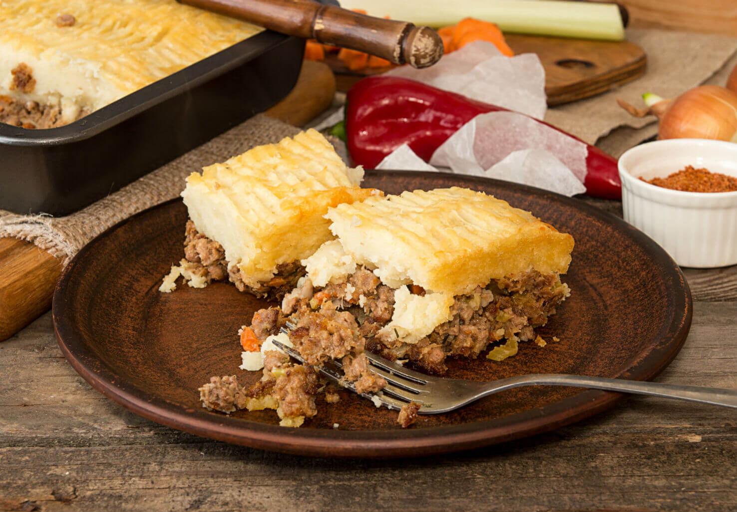Slice of shepherd's pie on plate by seasonings and pepper