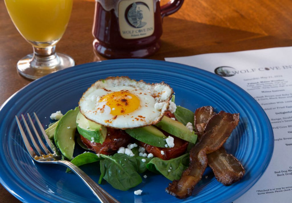 Fresh breakfast with fried egg, bacon, and avocado
