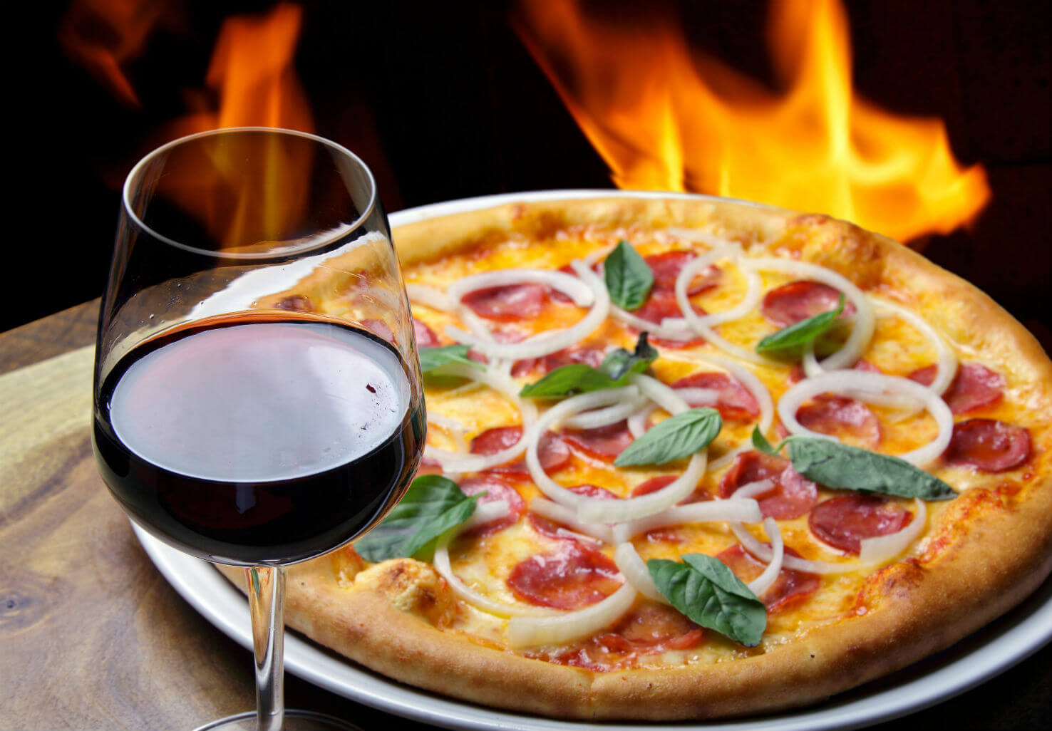 Fancy pizza near fire oven with wine glass