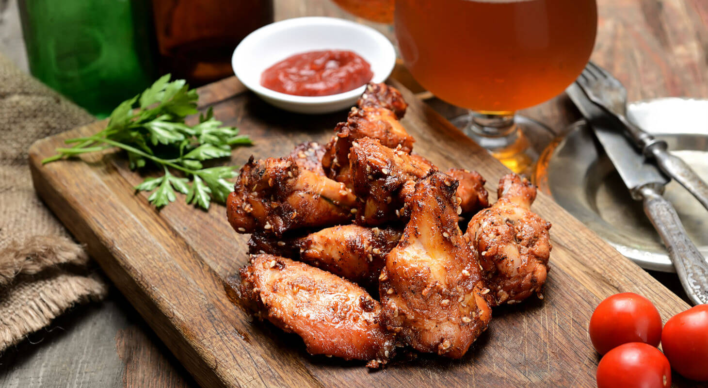 Artisan hot wings on plate with sauces and beer